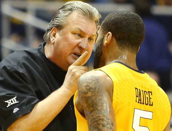 West Virginia coach Bobby Huggins talks to West Virginia guard Jaysean Paige (5), during a break in action in the 