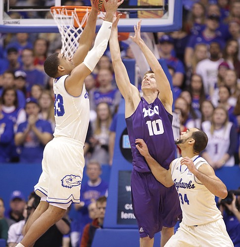 Kansas forward Landen Lucas (33) grabs a rebound over TCU forward Vladimir Brodziansky (10) during the first half, Saturday, Jan. 16, 2016 at Allen Fieldhouse. At right is Kansas forward Perry Ellis (34).