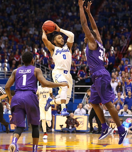 Kansas guard Frank Mason III (0) elevates to throw a pass around TCU forward Chris Washburn (33) during the second half, Saturday, Jan. 16, 2016 at Allen Fieldhouse. At left is TCU guard Chauncey Collins (1).