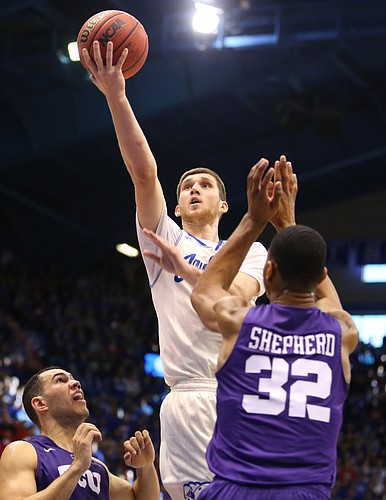 Kansas guard Sviatoslav Mykhailiuk (10) floats in for a bucket over TCU forward Karviar Shepherd (32) and guard Michael Williams (2) during the second half, Saturday, Jan. 16, 2016 at Allen Fieldhouse.