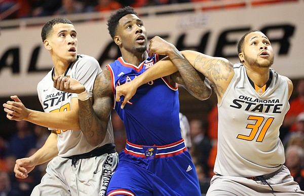 Kansas forward Jamari Traylor wrestles for position with Oklahoma State guard Jeffrey Carroll, left, and forward Chris Olivier (31) during the first half, Tuesday, Jan. 19, 2016 at Gallagher-Iba Arena in Stillwater, Okla.