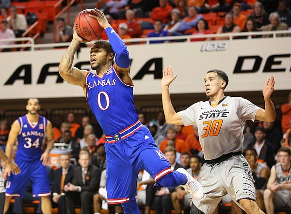 Kansas guard Frank Mason III (0) looks for an outlet after moving past Oklahoma State guard Jeffrey Carroll (30) during the first half, Tuesday, Jan. 19, 2016 at Gallagher-Iba Arena in Stillwater, Okla.
