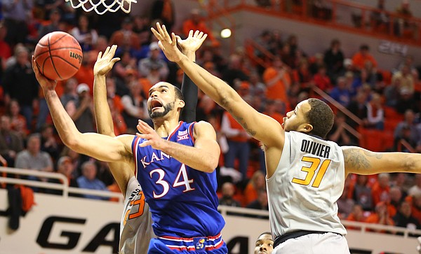 Kansas forward Perry Ellis (34) heads to the bucket past Oklahoma State forward Chris Olivier (31) during the second half, Tuesday, Jan. 19, 2016 at Gallagher-Iba Arena in Stillwater, Okla.