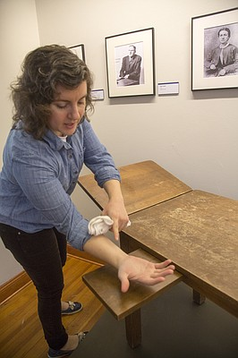 """Brittany Keegan, curator at Watkins Museum of History, 1047 Massachusetts St., shows off a 1930s-era exam table from Kansas University's Watkins Hospital (now known as the Watkins Student Health Center) in the museum's new """"Remedies and Memories"""" exhibit. The exhibit, which opens Friday, chronicles the history of medicine in Lawrence."""