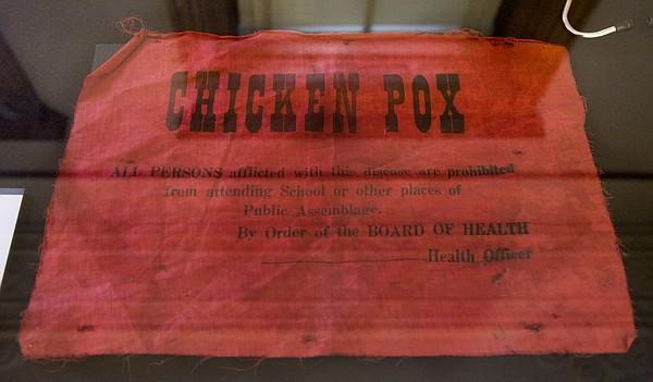 """In Lawrence's early years, red flags, like the one pictured here, were hung outside chicken pox-infected houses to warn passerby. The piece is one of many chronicling the history of medicine in Lawrence now on display at the Watkins Museum of History's """"Remedies and Memories"""" exhibit, opening Friday at the museum, 1047 Massachusetts St."""