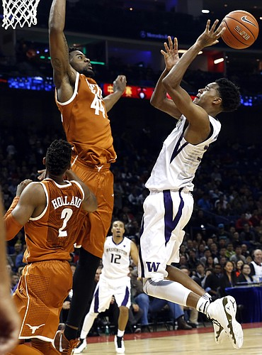 Dejounte Murray of the Washington Huskies tries to throw past Prince Ibeh of the Texas Longhorns during a match at the Mercedes Benz Arena in Shanghai, China, Saturday, Nov. 14, 2015. The University of Texas and University of Washington played the first-ever regular-season college men's basketball game in China at Shanghai's Mercedes Benz Arena, organized by the Pac-12 conference in partnership with Chinese tech giant Alibaba Group. (AP Photo/Ng Han Guan)