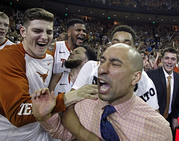 Texas head coach Shaka Smart, right, celebrates with Ryan McClurg, left, and Javan Felix, center, and Cameron Ridley, center rear, after beating North Carolina in an NCAA college basketball game, Saturday, Dec. 12, 2015, in Austin, Texas. Texas won 84-82. (AP Photo/Michael Thomas)