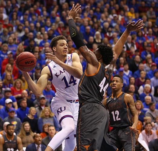Kansas guard Brannen Greene (14) looks to throw a pass around Texas center Prince Ibeh (44) during the first half, Saturday, Jan. 23, 2016 at Allen Fieldhouse.