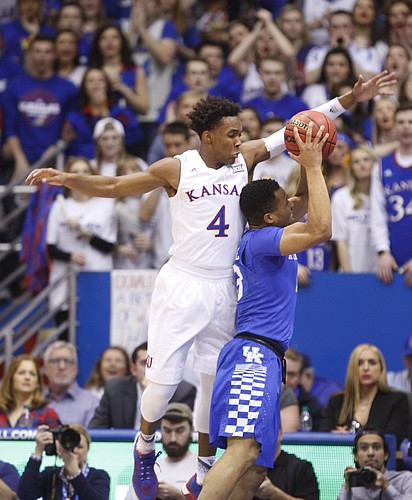 Kansas guard Devonte' Graham (4) gets over the top of Kentucky guard Isaiah Briscoe (13) during the first half, Saturday, Jan. 30, 2016 at Allen Fieldhouse.