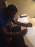 New KU DB Ian Peterson signing his letter early Wednesday morning.
