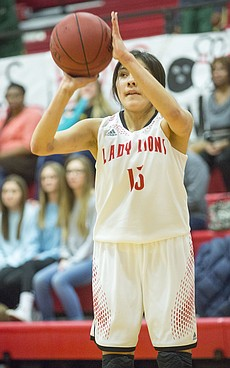 Lawrence High sophomore sharpshooter Talima Harjo lines up a three pointer during the Lions' game against Shawnee Mission South Friday evening at LHS.