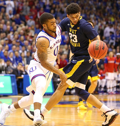 Kansas guard Frank Mason III (0) collides with West Virginia forward Esa Ahmad (23) while going for a loose ball during the first half, Tuesday, Jan. 9, 2016 at Allen Fieldhouse.