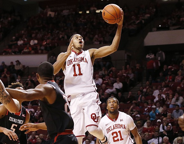 Oklahoma guard Isaiah Cousins (11) shoots between Texas Tech guard Toddrick Gotcher, left, and Oklahoma's Dante Buford, right, during the second half of an NCAA college basketball game in Norman, Okla., Tuesday, Jan. 26, 2016. Oklahoma won 91-67. (AP Photo/Sue Ogrocki)