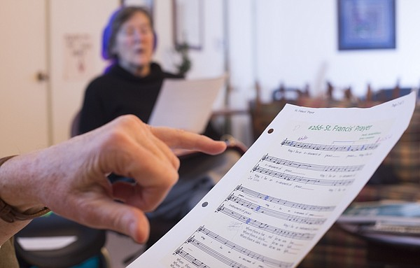 "Jean Drumm points to a verse in ""St. Francis' Prayer"" to follow along while Sophia Compton sings on Wednesday, Feb. 10, 2016 at Oread Friends Meeting House, 1146 Oregon St. The women are members of the Sunflower Threshold Choir, the Lawrence branch of a nation network of choirs dedicated to singing for those at the threshold of life."