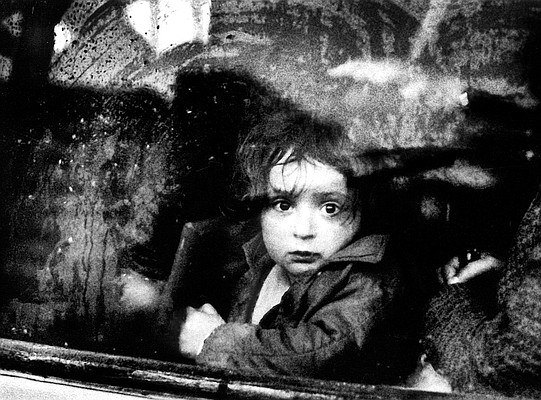 A Face in the Window — A young girl stares through a clouded bus window during a heavy thunderstorm in Tirana, Albania. When I moved closer to the bus she turned away crying. In 1991, I was with a group of Westerners who were among the first foreigners allowed in the country since World War II. If I were made to choose a favorite photograph, this would be it.