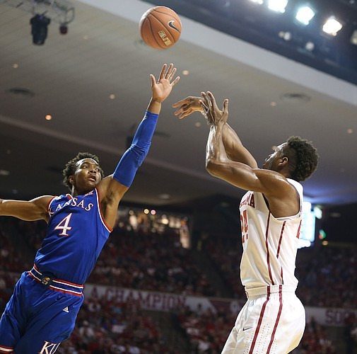 Kansas guard Devonte' Graham (4) lunges to defend against a three from Oklahoma guard Buddy Hield (24) during the first half, Saturday, Feb. 13, 2016 at Lloyd Noble Center in Norman, Okla.