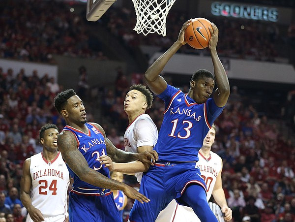 Kansas forward Cheick Diallo (13) pulls a rebound away from Oklahoma center Jamuni McNeace (4) during the first half, Saturday, Feb. 13, 2016 at Lloyd Noble Center in Norman, Okla. At left is Kansas forward Jamari Traylor (31).