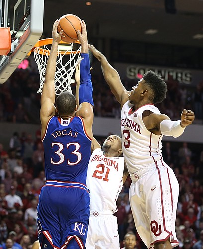 Kansas forward Landen Lucas (33) gets up for a jam against Oklahoma guard Christian James (3) and forward Dante Buford (21) during the second half, Saturday, Feb. 13, 2016 at Lloyd Noble Center in Norman, Okla.
