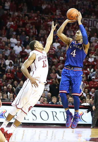 Kansas guard Devonte' Graham (4) puts a three over Oklahoma guard Isaiah Cousins (11) during the second half, Saturday, Feb. 13, 2016 at Lloyd Noble Center in Norman, Okla.