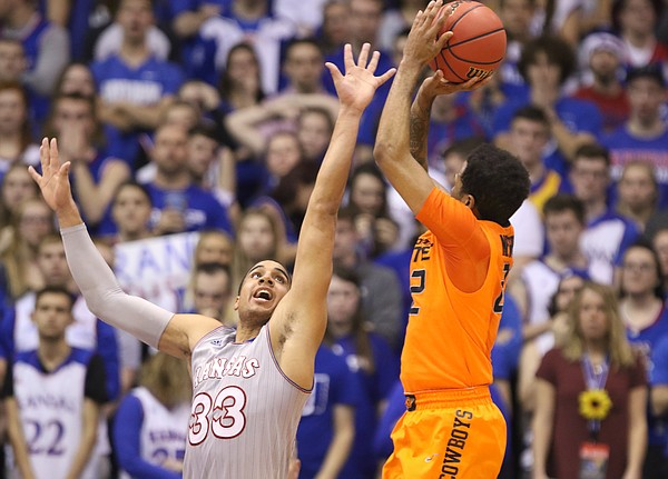 Kansas forward Landen Lucas (33) gets in the face of Oklahoma State guard Jeff Newberry (22) on a shot during the second half, Monday, Feb. 15, 2016 at Allen Fieldhouse.