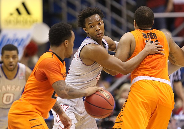 Kansas guard Devonte' Graham looks to move around Oklahoma State forward Chris Olivier (31) as he defends against Oklahoma State guard Tyree Griffin (2) during the first half, Monday, Feb. 15, 2016 at Allen Fieldhouse.