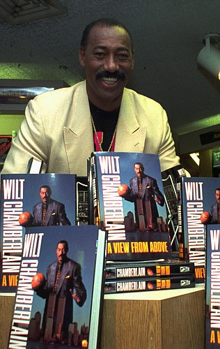 "Wilt Chamberlain poses with copies of his book ""A View From Above"" at New York's Waldenbooks store Oct. 28, 1991."