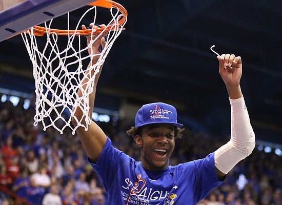 Kansas guard Devonte' Graham (4) holds up his share of the net as Jayhawks celebrate locking up a share of their twelfth-straight Big 12 title following their 67-58 win over the Red Raiders, Saturday, Feb. 27, 2016 at Allen Fieldhouse.