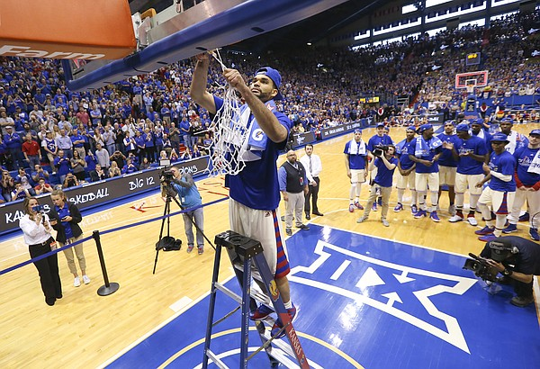 Kansas forward Perry Ellis finishes off the net as his teammates and the fieldhouse stand to watch as the Jayhawks celebrate locking up a share of their twelfth-straight Big 12 title following their 67-58 win over the Red Raiders, Saturday, Feb. 27, 2016 at Allen Fieldhouse.