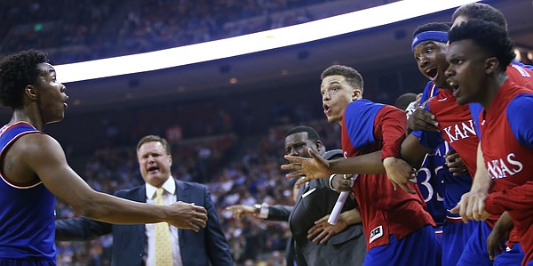 From the KU bench from left, Brannen Greene, Carlton Bragg Jr., Sviatoslav Mykhailiuk and Lagerald Vick, greet Devonte' Graham, left and react to a dunk by Jamari Traylor on a pass from Graham in the 2nd-half of a Jayhawk 86-56 win over the Texas Longhorns Monday, Feb. 29, 2016 at the Frank Erwin Center in Austin, Texas.
