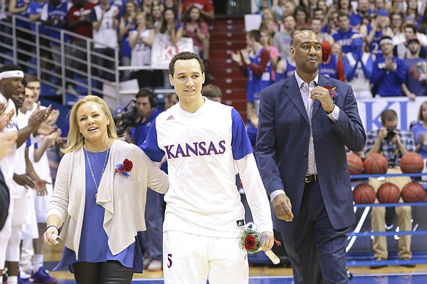 Kansas guard Evan Manning walks with his mother Julie Manning, followed by his father Danny Manning as they are introduced to the fieldhouse on Saturday, March 5.