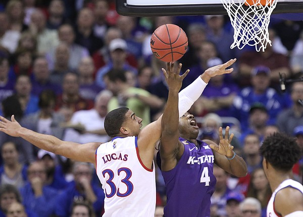 Kansas forward Landen Lucas (33) disrupts a shot from Kansas State forward D.J. Johnson (4) during the first half, Thursday, March 10, 2016 at Sprint Center in Kansas City, Mo.