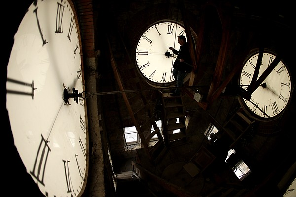Custodian Ray Keen inspects a clock face before changing the time on the 100-year-old clock atop the Clay County Courthouse Saturday, March 8, 2014, in Clay Center, Kan.