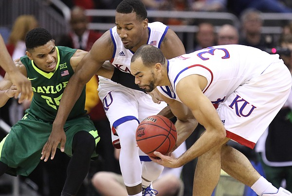 Kansas forward Perry Ellis comes away with a loose ball after wrestling it away from Baylor guard Al Freeman (25) during the first half, Friday, March 11, 2016 at Sprint Center in Kansas City, Mo. Also pictured is Kansas guard Wayne Selden Jr. (1).