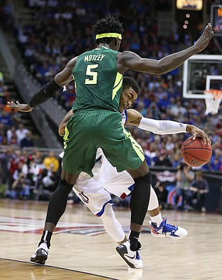 Kansas guard Frank Mason III (0) slams into Baylor forward Johnathan Motley (5) during the first half, Friday, March 11, 2016 at Sprint Center in Kansas City, Mo.