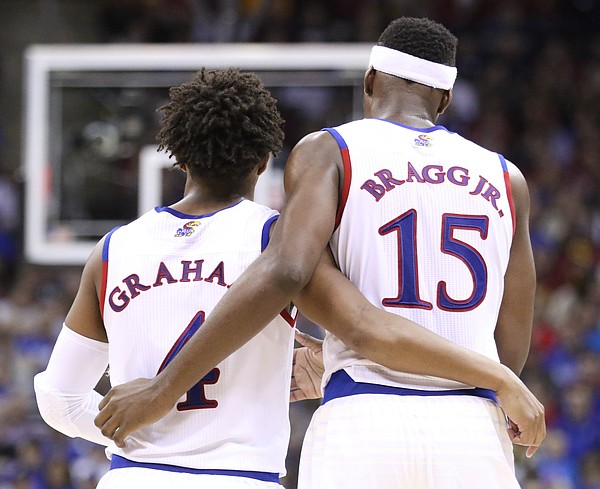 Kansas guard Devonte' Graham and forward Carlton Bragg Jr. converse during the second half, Friday, March 11, 2016 at Sprint Center in Kansas City, Mo.