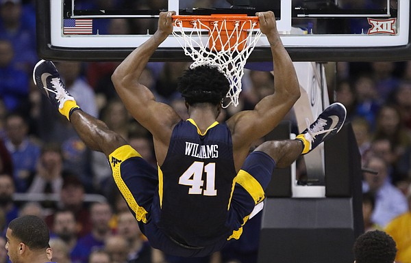 West Virginia forward Devin Williams (41) takes his time coming down from the rim after a dunk against Kansas during the first half, Saturday, March 12, 2016 at Sprint Center in Kansas City, Mo.