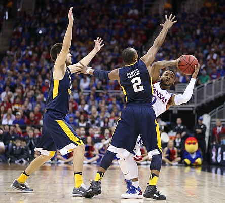 Kansas guard Frank Mason III (0) tries to fight through a trap from West Virginia guard Jevon Carter (2) and forward Nathan Adrian (11) during the first half, Saturday, March 12, 2016 at Sprint Center in Kansas City, Mo.