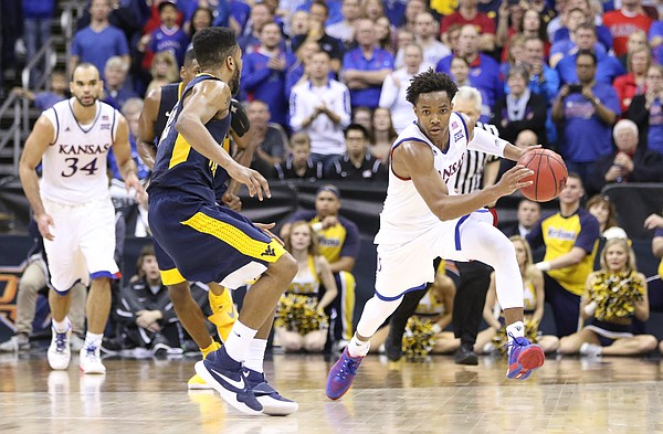 Kansas guard Devonte' Graham (4) pushes the ball up the court against West Virginia guard Tarik Phillip during the second half, Saturday, March 12, 2016 at Sprint Center in Kansas City, Mo.