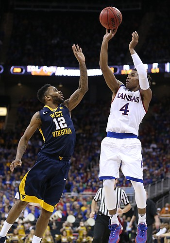Kansas guard Devonte' Graham (4) puts a three over West Virginia guard Tarik Phillip (12) during the second half, Saturday, March 12, 2016 at Sprint Center in Kansas City, Mo.