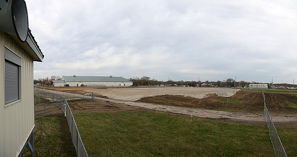 Current construction work at the Douglas County Fairgrounds includes clearing land for a 52,000-square-foot Open Pavilion to be located on the fairgrounds' north side, directly east of the indoor arena. The pavilion will be open for spring, summer and fall. During the county fair, it will be used to house animals. This view is looking west from near the derby arena toward the current indoor community building in background at left. The site of the new pavilion will be in the cleared area at center.