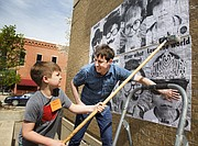Dexter Dillingham, 8, left, and Neal Barbour, director of youth education at the Lawrence Arts Center, put some guerrilla art — aka student posters — on the walls of US Bank, 900 Massachusetts St., on Wednesday afternoon, March 16, 2016.
