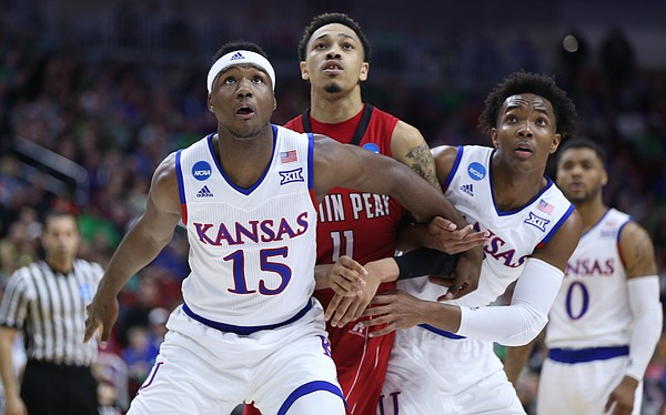 Kansas forward Carlton Bragg Jr. (15) and guard Devonte' Graham (4) box out Austin Peay guard Khalil Davis (11) during the first half of a first-round NCAA Tournament game, Thursday, March 17, 2016 at Wells Fargo Arena in Des Moines, Iowa.