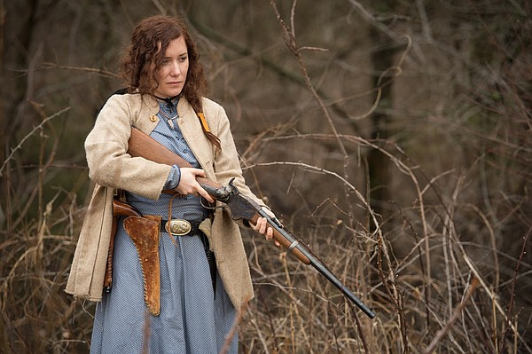 "Actress Alexandra Goodman, in costume as Kitty Mae, brandishes her character's weapons of choice in this behind-the-scenes image from ""Red Bird."" The new web series, which tells the tale of frontier woman Kitty Mae's quest to avenge her murdered son, premieres Thursday."