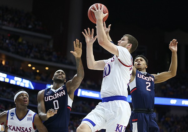 Kansas guard Sviatoslav Mykhailiuk (10) gets to the bucket between Connecticut forward Phillip Nolan (0) and guard Jalen Adams (2) during the first half on Saturday, March 19, 2016 at Wells Fargo Arena in Des Moines. At left is Kansas forward Carlton Bragg Jr.