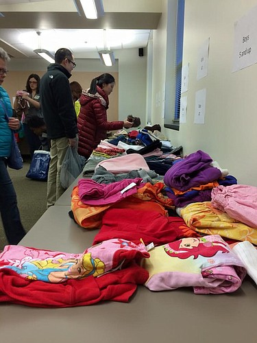 Families browse through clothes during a Clothes Swap at the Lawrence-Douglas County Health Department.