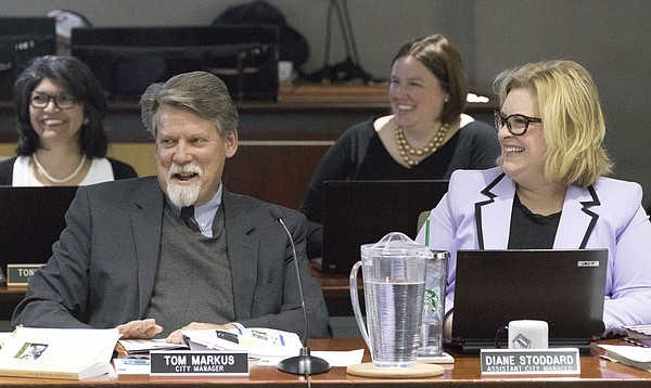 New Lawrence City Manager Tom Markus flashes a smile as he is introduced at a City Commission meeting in March at City Hall. Seated next to Markus is Assistant City Manager Diane Stoddard.