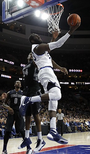 Villanova's Daniel Ochefu (23) goes up for a shot past Georgetown's Marcus Derrickson (24) during the first half of an NCAA college basketball game, Saturday, March 5, 2016, in Philadelphia. (AP Photo/Matt Slocum)