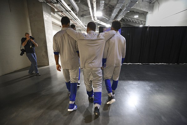 Kansas guard Frank Mason III rests his elbows on the shoulders of teammates Wayne Selden Jr., left, and Devonte' Graham as the starting five make their way toward interviews with media members on Friday, March 25, 2016 at KFC Yum! Center in Louisville, Kentucky.