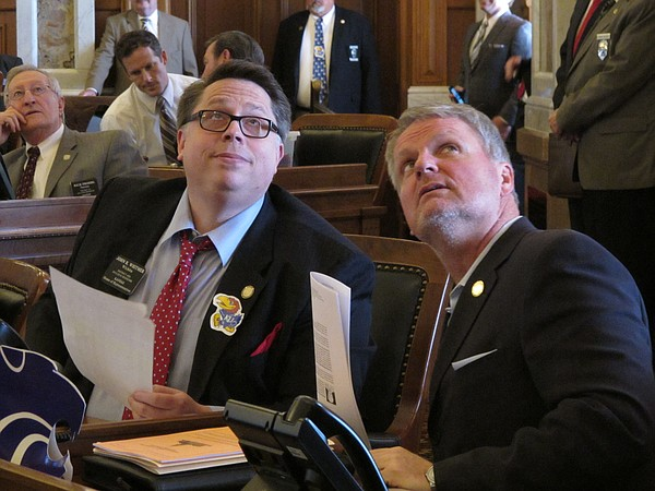 Kansas state Reps. John Whitmer, left, R-Wichita, and Marc Rhoades, right, R-Newton, watch one of the House's electronic tally boards as members vote to approve a Republican school funding plan, Thursday, March 24, 2016, at the Statehouse in Topeka, Kan. (AP Photo/John Hanna).