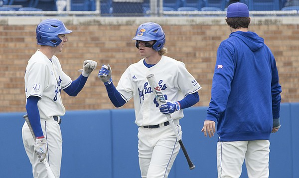 Kansas freshman Rudy Karre, center, is congratulated by teammates as he walks back to the dugout after scoring a first inning run during the Jayhawks' game against West Virginia on Saturday at Hoglund Ballpark